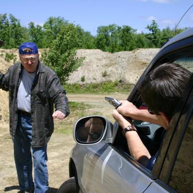 Man firing a gun out of a car window at a knife wielding attacker
