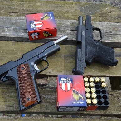 Two pistol with an open box of Honor Defense ammunition