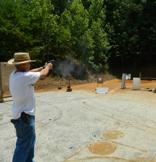 Man firing a handgun at an outdoor range