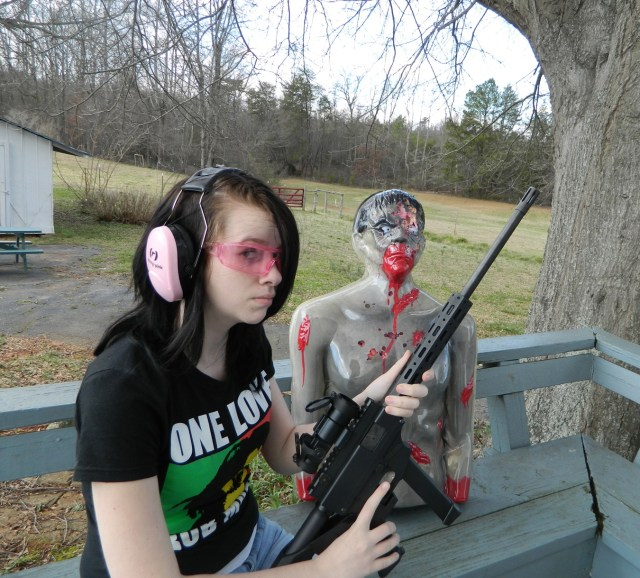 Woman holding a pistol caliber carbine with a zombie target in the rear