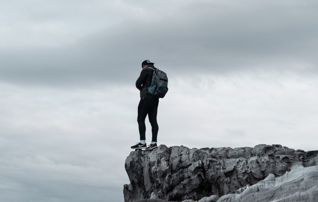 Man on cliff with Bug-Out Bag