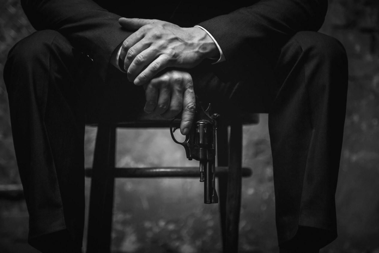 Best Correct Gun Movies Man in chair holding revolver