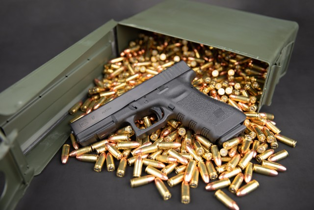 Glock 17 pistol on Ammo with a tipped over green Ammo Can