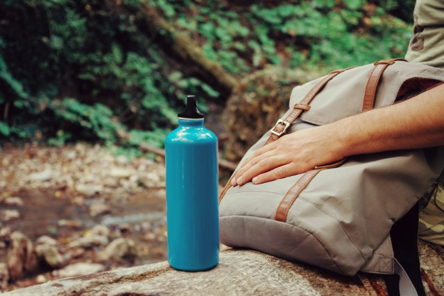 Unrecognizable hiker man sitting with backpack and stainless eco bottle of water on nature outdoor.