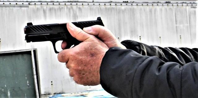man shooting semi-auto handgun