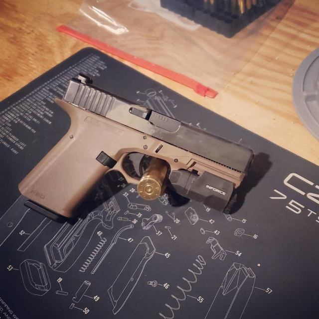 Brown GLOCK pistol on shop mat