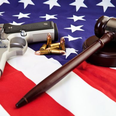 Photo of gavel, gun, and bullets over an American flag NRA
