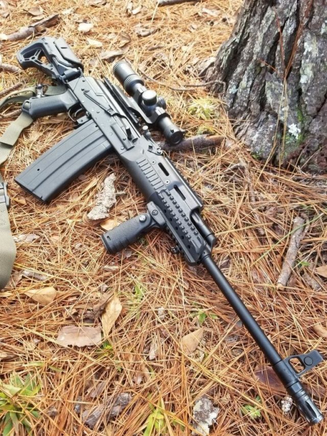 Ak rifle with scope on woods ground