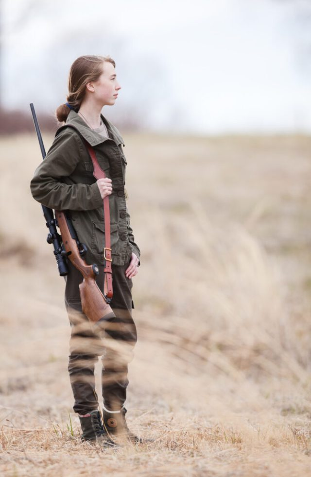 woman holding rifle in field