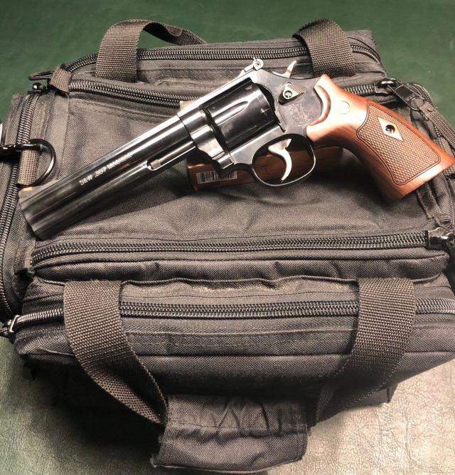 six inch blued revolver on black range bag