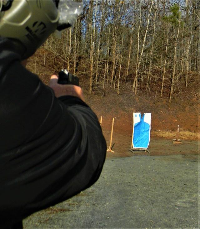 Man firing pistol at target
