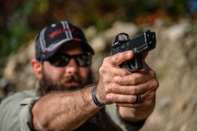 man shooting pistol with red dot sight