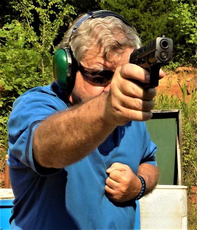 man firing pistol drills with one hand