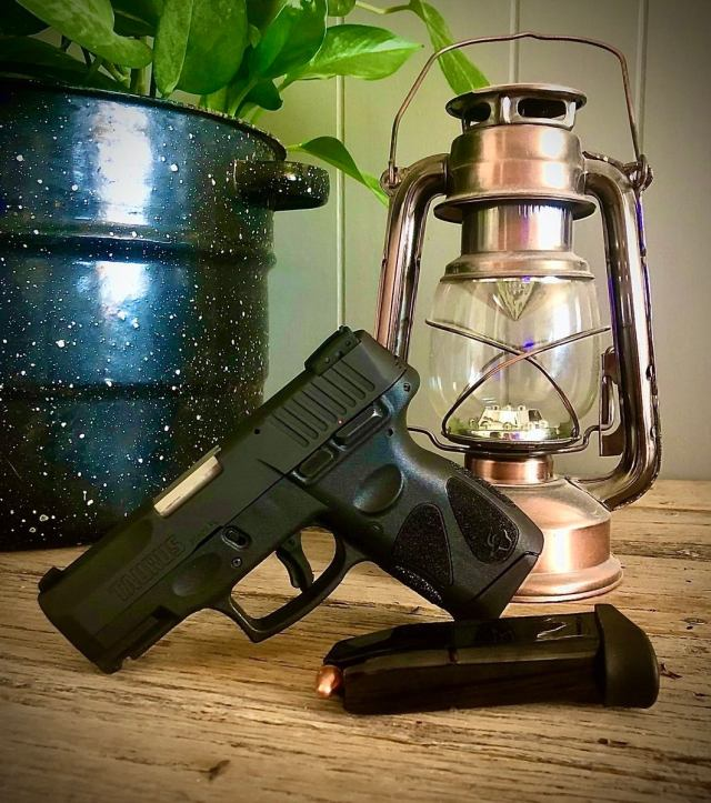 taurus pistol on table with mag, lamp and plant
