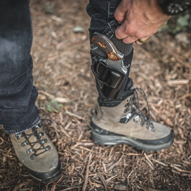 man in jeans and boot with revolver on ankle