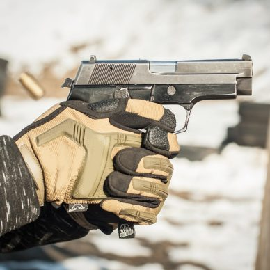 Close-up detail view of hands in gloves holding gun. Shooting range