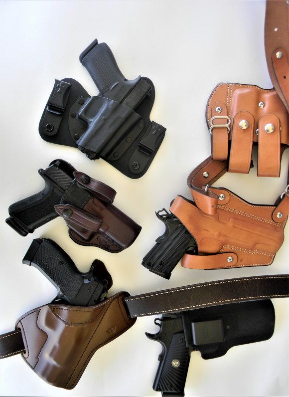 several pistol in different types of holsters