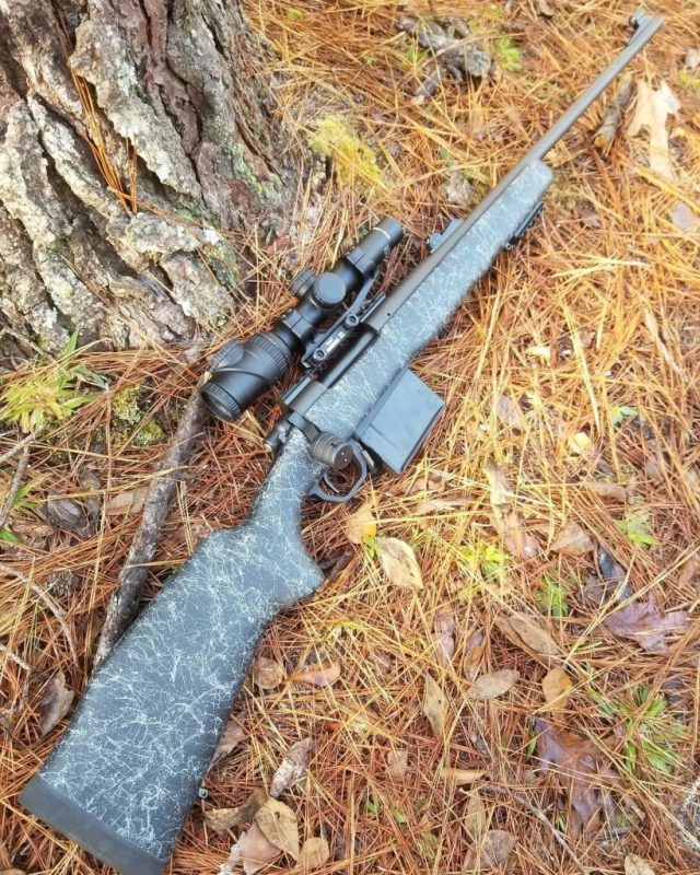 Bolt-action rifle with scope on ground by tree