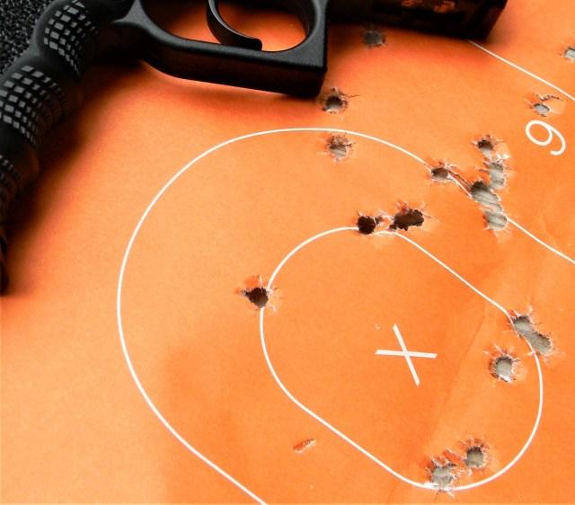 Pistol on Orange Target with Bullet Holes