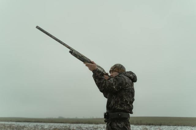 man pointing hunting shotgun