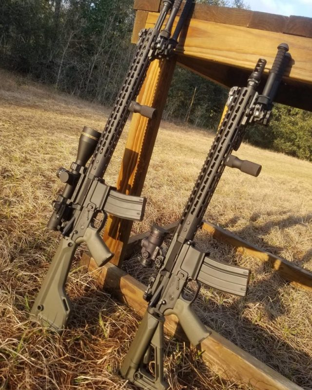 two AR-15s leaning on wood deck