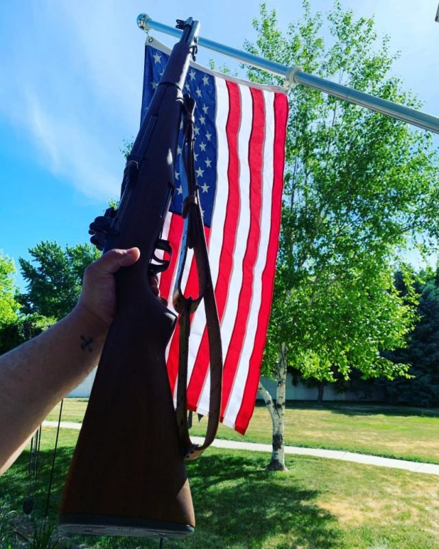 Old military rifle in front of American flag