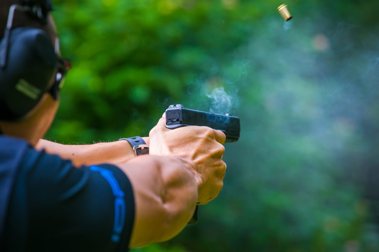 Man firing a pistol with spent cartridge ejecting