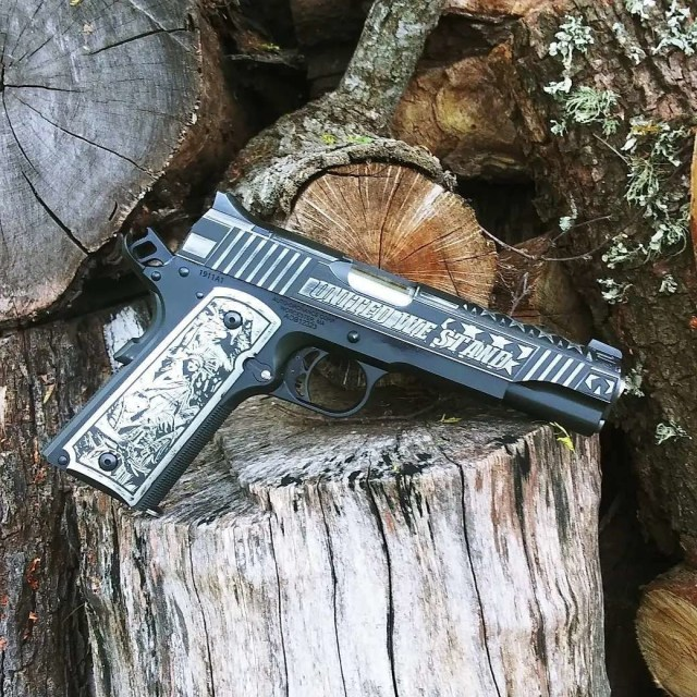 engraved 1911 pistol on tree stump
