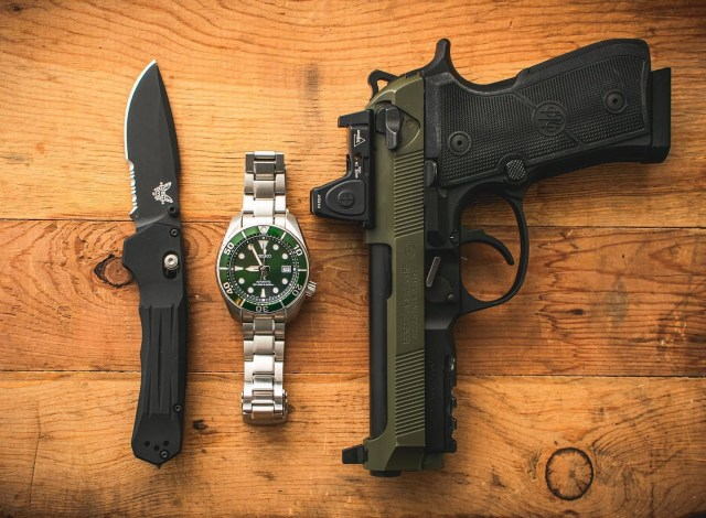 Pistol, knife and watch on table