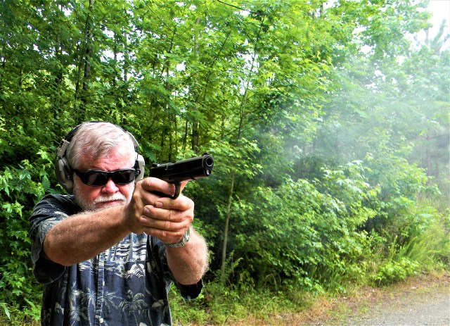 bob campbell wearing safety glasses and hearing protection while smoke bellows from a 1911 pistol