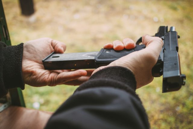 Close-up of a man hands holding and loading gun magazine in the pistol at the shooting range.