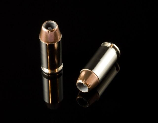 2 40 caliber bullets on a black reflective background