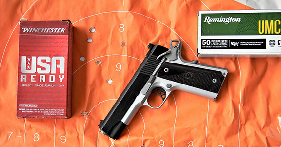 Springfield Ronin Operator Commander on an orange silhouette target with Winchester USA and Remington UMC ammunition boxes