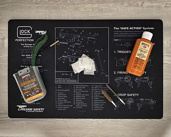 Glock themed gun cleaning mat with Hoppe's 9 gun oil and bore snake