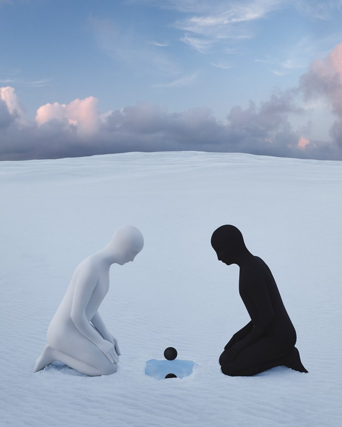 Two people look to a black ball and pool of water