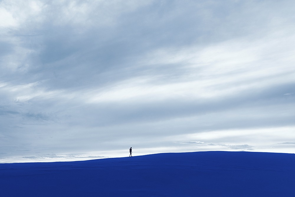 Gabriel Isak photo: Man walking on blue sand