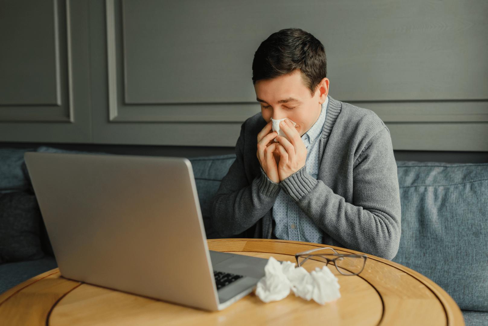 gripe homem limpando o nariz em frente ao computador