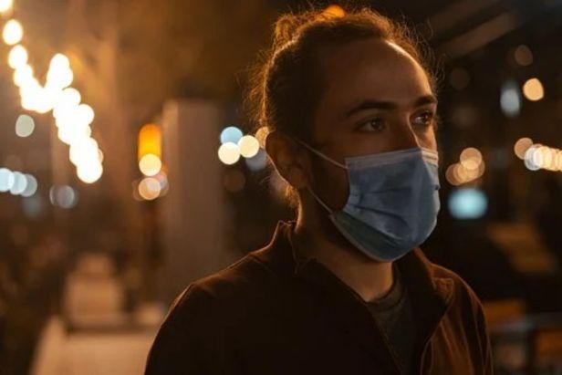 hombre joven usando cubrebocas noche