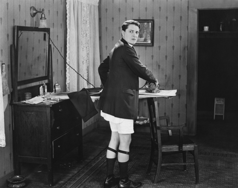 Man in sock garters ironing