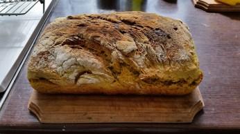 Pâinea casei, făcută cu mare pricepere de Iulia, din faina integrală de grâu, mălai, tărâțe, turmeric, diverse plante aromate și dospită-încet cu maia