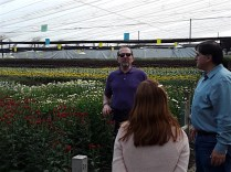 Tom Royer (background) discusses production with farm officials.