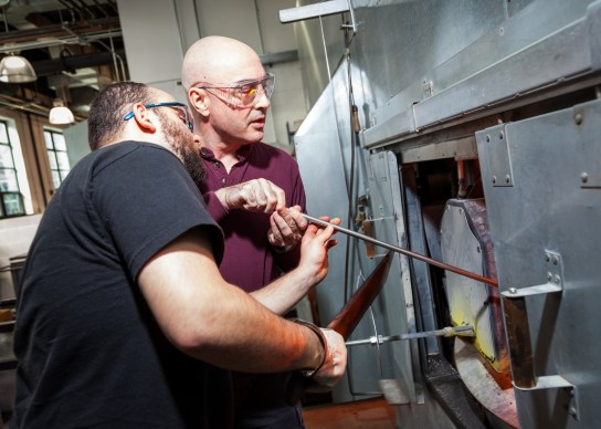 Chris Giordano assists a local Veteran in gathering glass from the furnace