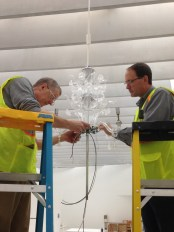 Museum staff putting together Evening by Cerith Wyn Evans, a colorless double-tiered glass chandelier.