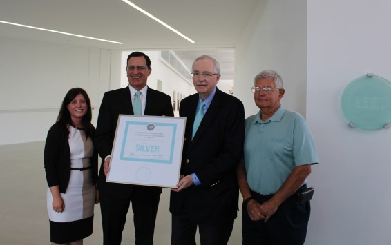 Lauren Staniec, board chair of the NY Upstate Chapter of the U.S. Green Building Council presents the certification to Alan Eusden, COO of CMoG; Jim Flaws, vice chairman of CMoG's board, and former vice-chairman and CFO of Corning Incorporated; and Joe Dubendorfer, project manager for the new wing.