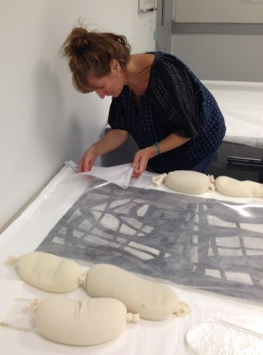 Luisa Casella from West Lake Conservators checks a photograph that has been humidifying to see if it is ready to be transferred to the flattening table.