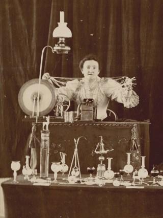 A glassworker, possibly Mrs. F.A. Owen, holds up spun glass.