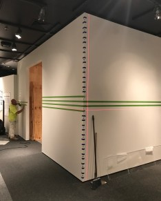Painting the wall stripes in the exhibition.