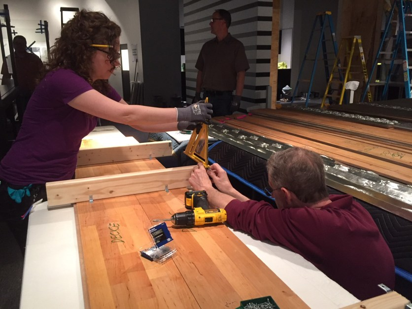 Preparators Lindsay and Steve brace ceiling panels with 2x4s, to attach in sections to the plywood ceiling.