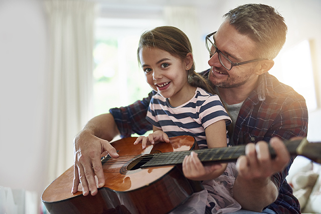 Shot of a little girl playing the guitar with her father