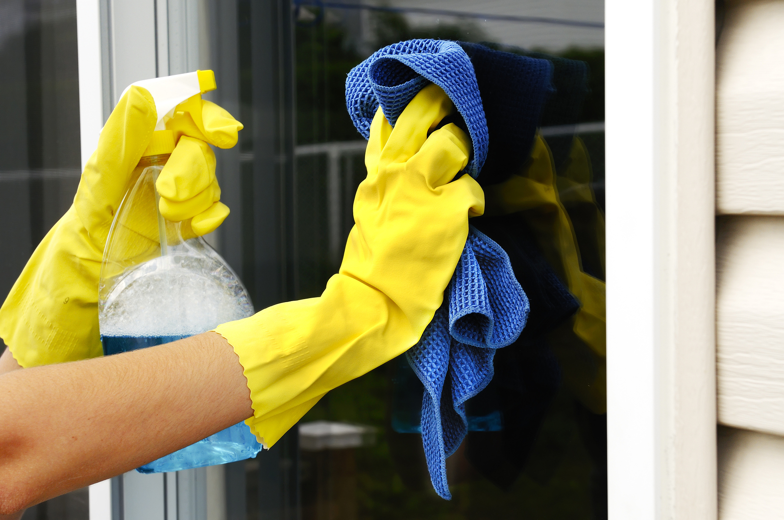 woman polishing glass door using microfiber cloth and yellow latex gloves